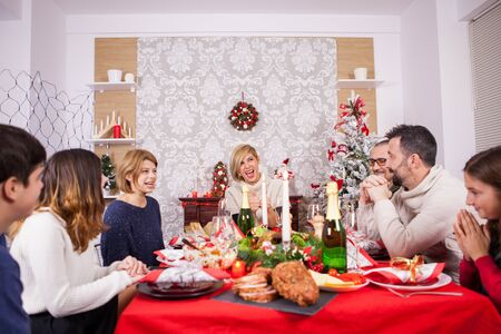 Beautiful family with children eating christmas dinner. Traditional meal for christmas. Christmas tree. Happy family celebrating christmas.