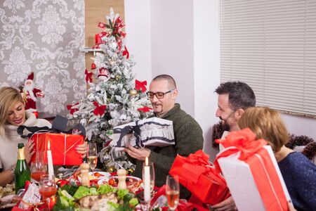 Large family happy about their christmas gifts. Christmas tree. Traditional christmas meal. Father excited about his christmas gift.