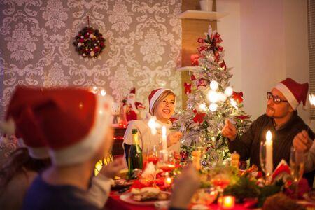 Hermosa joven madre con fuegos artificiales de mano sonriendo y mirando a su hermano mayor en la fiesta de Navidad. Feliz alrededor de la cena de Navidad con la familia grande. Foto de archivo
