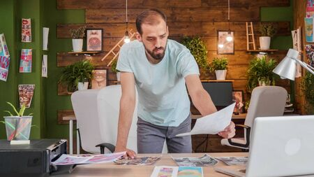 Young designer who is leaning over the table and looks at some pictures printed on the table. Young busy artist