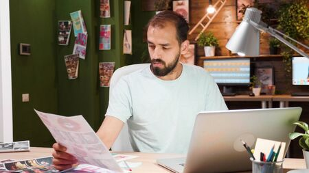 Young designer who looks at a printed picture and has a laptop on the desk. Creativ desegner and modern office