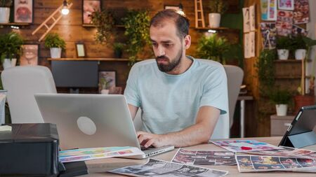 Young designer working on a laptop in a creative and cozy space. Creative agency and cool work space