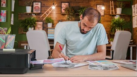 Designer boy who sits at the desk and makes some notes on some printed sheets. Loft office