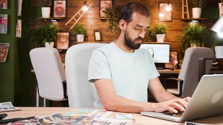 Young designer working in a cozy office on a laptop. Smart and modern office