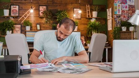 Young designer in front of some printed sketches and making notes. Modern agency office Reklamní fotografie