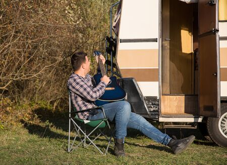 Happy hipster young man relaxing playing on guitar in front of his retro camper van in the mountains.