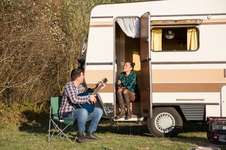Happy couple enjoying their relationship in the mountains with their retro camper van.