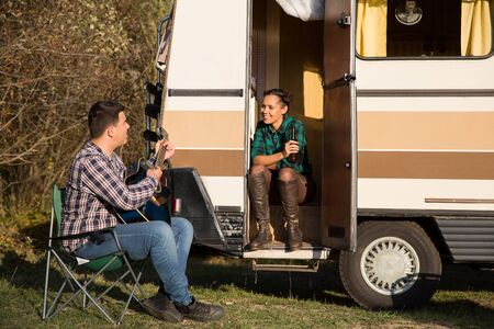Hipster couple relaxing with a guitar song in front of their retro camper van. Couple relaxing in the mountains.