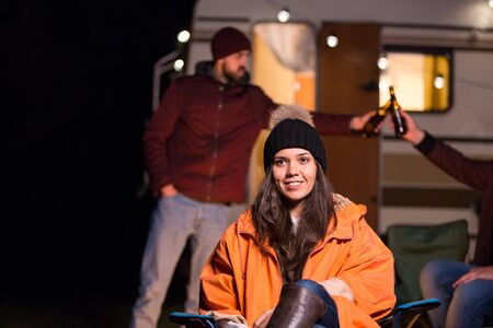 Portrait of young girl in front of retro camper van with friends clinking beer in the background. Reklamní fotografie