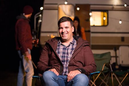 Portrait of tourist sitting on a camping chiar in the mountains with retro camper van in the background. Friends making camp fire stronger. Reklamní fotografie