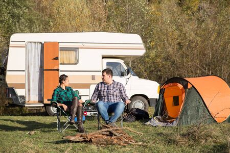 Couple relaxing together in campsite in the mountains with their retro camper van in the background.