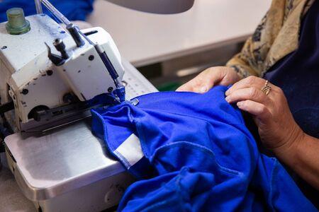 Gros plan avec les mains sur une femme travaillant sur une machine à coudre. Matière textile bleue Banque d'images