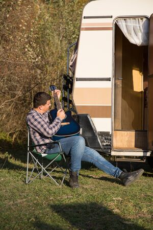 Young man singing music on his guitar in the mountains in front of his retro camper van.