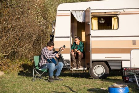 Man playing playing some good music on guitar to his girlfriend in front of their retro camper van.