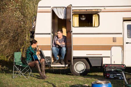 Beautiful young girlfriend singing for her boyfriend in front of their retro camper van. Happy couple. 版權商用圖片