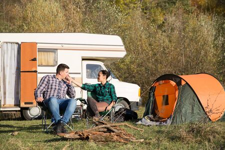 Boyfriend kissing the hand of his girlfriend on camping site with retro camper van in the background. Reklamní fotografie