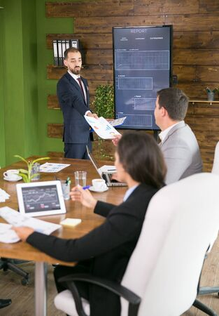 Business meeting and presentation in modern conference room for colleagues. Businessman in suit.