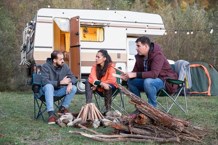 Group of friends escaping from city agitation and camping in the mountains with their retro camper van.