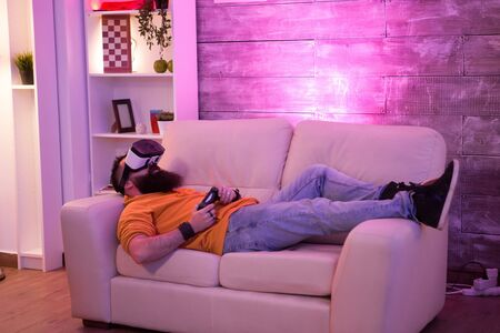 Male sitting on couch with virtual reality goggles in a room with colorful neon light.