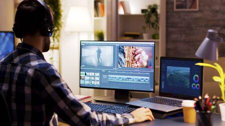 Cinéaste pointant sur le moniteur dans le bureau à domicile tout en travaillant sur la post-production d'un film. Éditeur vidéo portant des écouteurs.