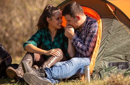 Boyfriend kissing his girlfriends hand in front of the tent. Happy atmosphere Reklamní fotografie