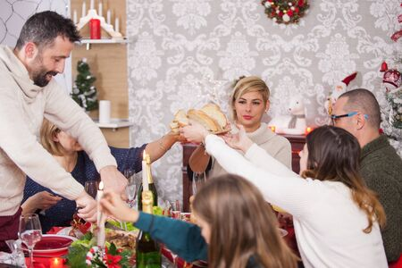 Adult man slicing meat while family members are passing the bread to each other on christmas eve. Happy young family dining together on christmas. Christmas tree. Beautiful children.