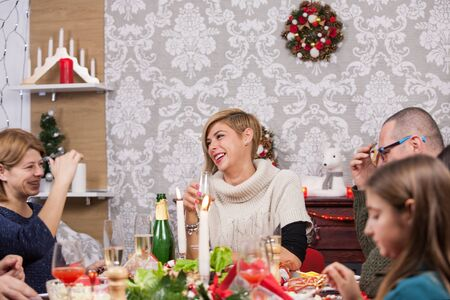 Beautiful young woman laughing with her sister and laughing together at christmas celebration. Beautiful family dining together at christmas feast.