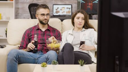 Beautiful young couple sitting on the couch enjoying chips and soda while watching tv at night. Banque d'images