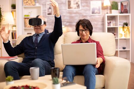 Old elderly retired man using VR virtual reality headset in their cozy apartment.