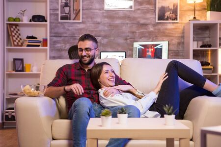 Cheerful young couple laughing while watching a tv show on tv at night. Couple sitting on sofa.