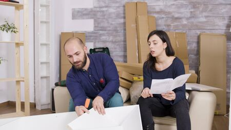 Couple assembling furniture using instructions in their new apartment. Couple working as a team.