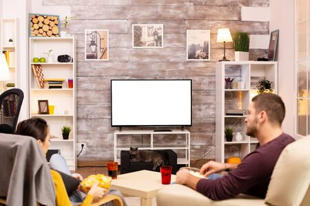 Couple looking at isolated TV screen in cozy living room while eating takeaway food