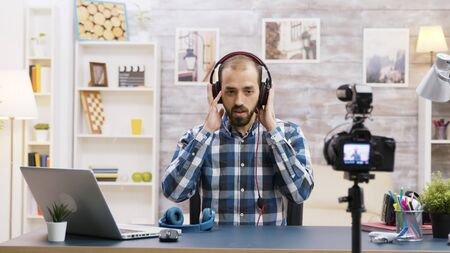 Famous vlogger recording a review and testing headphones. Creative content creator.
