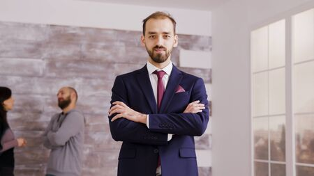 Real estate agent in business suit holding arms crossed and smiling to the camera in an an empty apartment with couple in the background. Фото со стока - 137738224