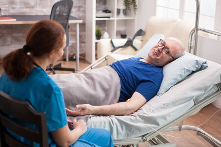 Male pensioner in nursing home talking with female doctor sitting on bed.