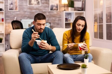 In modern cozy living room couple is enjoying takeaway noodles while watching TV comfortably on the sofa Stock fotó