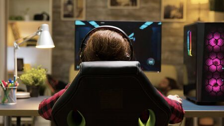 Dolly shot of woman sitting on gaming chair playing computer games. Man lying on sofa in the background. Reklamní fotografie