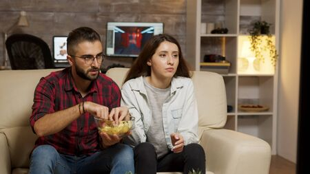 Caucasian young couple eating chips while watching television. Couple looking concerned at television.