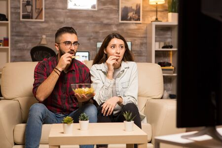Couple eating chips and looking shocked at tv while watching a movie at night.