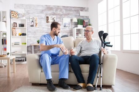 Young male nurse in nursing home with pills for senior man with crutches sitting on couch. Stock Photo