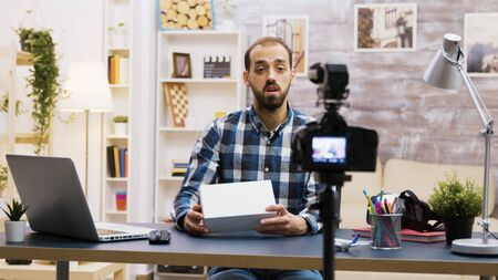 Handsome bearded vlogger recording a review while holding a box. Online content creator.