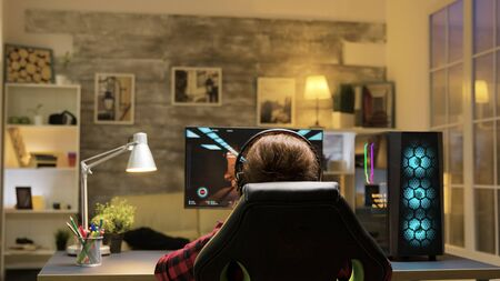 Female gamer celebrating victory with hands raised on computer games. Man relaxing on sofa watching tv in he background.
