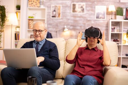 Old elderly retired woman in her 60s experiencing virtual reality for the first time in their cozy apartment Stockfoto