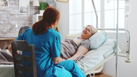 In bright retirement home old lady lying in hospital bed talks with a female caregiver.