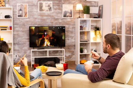 Back view of couple in living room watching a movie on the TV while eating takeaway food Stock fotó