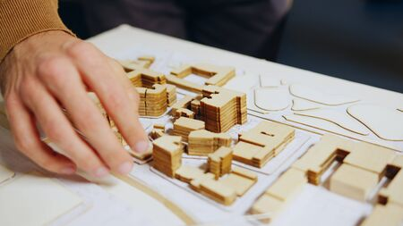 Close up of architect hand checking city model concept in his home office.