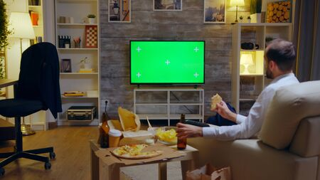 Back view of businessman enjoying his pizza while watching to a TV with Mock Up green screen Stockfoto