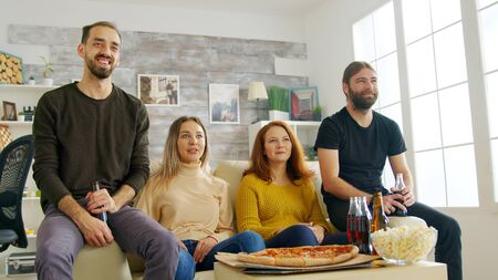 Group of friends celebrating victory of football match in living room. Young man cheering and holding a pizza.