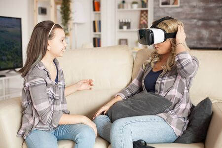 Excited little girl about her mother using virtual reality headset.