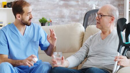 Male nurse giving pills to retired man in nursing home.